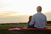 Father and daughter (2-3 years) enjoying sunset, English Garden, Munich, Bavaria, Germany