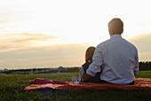 Vater und Tochter beobachten Sonnenuntergang, Englischer Garten, München, Bayern, Deutschland