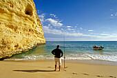 Angler on the beach under blue sky, Praia da Marinha, Algarve, Portugal, Europe