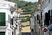 Street with houses in Es Mercadal leading towards a hill, Minorca, Balearic Islands, Spain