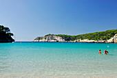 People swimming in the sea, sandy beach and turquoise sea at Cala Galdana, Menorca, Balearics, Spain