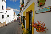 White painted houses and flower decorations in Ferreries, Minorca, Balearic Islands, Spain