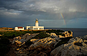 Lighthouse with rainbow and clouds at Cap de Cavallaria, Minorca, Balearic Islands, Spain