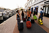 Spanish tourists on the way to the ferry, Marina Ciutadella, Minorca, Balearic Islands, Spain