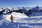 Woman backcountry skiing ascending snow ridge, Kitzbuehel range, Tyrol, Austria