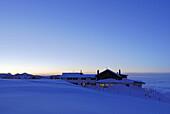 Snow-covered alpine lodge in dusk, Steinlingalm, Kampenwand, Chiemgau range, Chiemgau, Bavaria, Germany