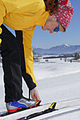 Cross-country skier closing binding, Walchsee, Kaiser range, Tyrol, Austria