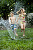 Young boy and girl running through a yard sprinkler