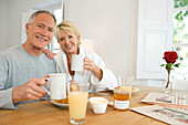 Adult, Adults, At home, Breakfast, Breakfasts, Caucasian, Caucasians, Coffee, Color, Colour, Contemporary, couple, couples, Cup, Cups, Daytime, Facing camera, female, Glass, Glasses, grin, grinning, happiness, happy, Hold, Holding, Home, human, indoor, in