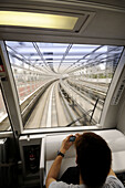 Automated guideway transit train (Yurikamome Line) on its track along the Rainbow Bridge (finished in 1993 with 570m./1870ft. long), going to Odaiba island. Tokyo Bay. Japan.