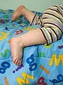 Baby's feet on an alphabet blanket