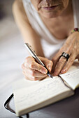 Adult, Adults, Color, Colour, Contemporary, detail, details, Diaries, Diary, Female, Fountain pen, Fountain pens, hand, hands, human, indoor, indoors, interior, Notebook, Notebooks, One, One person, Open, Page, Pages, Pen, Pens, people, person, persons, S