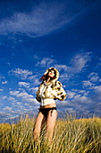 Adult, Adults, Alone, Bikini, Bikinis, Color, Colour, Contemporary, Country, Countryside, Daytime, exterior, Female, Grass, Grasses, Hands in pockets, Hood, Hoods, human, Jacket, Jackets, Model, Models, Odd, One, One person, Out of place, outdoor, outdoor