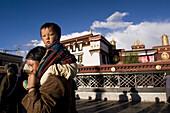 Mom carrying son around the Jokhang temple Kora (pilgrimage circuit) in old Lhasa, Tibet, China