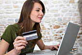 Adult, Adults, Bank card, Brunette, Brunettes, Caucasian, Caucasians, Color, Colour, Computer, Computers, Contemporary, Credit card, Credit cards, Dark-haired, Female, Hold, Holding, Human, Indoor, Indoors, Interior, Internet shopping, Laptop, Laptop comp