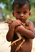 Sea gypsy, Moken boy carrying a chicken, Mergui Archipelago, Andaman Sea, Myanmar, Burma, Asia