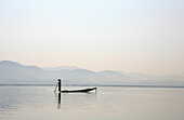 Intha fisherman with net standing in his boat, Inle Lake, Shan State, Myanmar, Burma, Asia