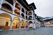 Rila monastery at dusk, lighted arcades of the residential building, Bulgaria