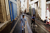 French. Provence. Marseille. Two local boys playing football in a street of Panier Quarter.