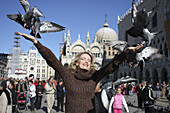 29 year old woman with pigeons in St Marks Square, Venice. Veneto, Italy