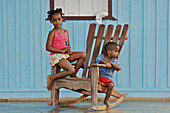 A boy and a girl sitting on a rocking chair on the porch of a house.