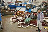Agadir, Morocco, port, trawler: repairing nets