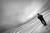 Pescador de caña en la playa, al atardecer. Costa Dorada (Tarragona). Spain.