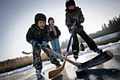 Children playing hockey on lake Buchsee, Munsing, Upper Bavaria, Germany