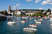 Zurich street parade weekend  in summer, party boats on river Limmat , background  Grossmunster,  Zurich, Switzerland