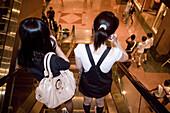 Asiatische Maedchen auf Rolltreppe im Ngee Ann City, Takashimaya shopping center, Orchard Road, Einkaufszentrum,  Singapur Asien