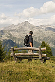 Hiker (MR) in the hiking area of Klausberg, view towards Zillertaler Alps, Tauferer Ahrntal, South Tyrol, Italy