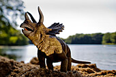 Toy triceratops at the shore of a lake