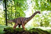 Toy saltasaurus in front of deciduous trees