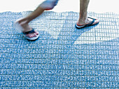 Adult, Adults, Anonymous, blurred, Color, Colour, Contemporary, Daytime, detail, details, exterior, Feet, Foot, Footgear, Footwear, From above, Ground, Grounds, human, Male, Man, Men, motion, movement, moving, One, One person, outdoor, outdoors, outside,