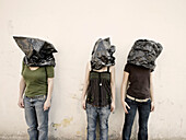 Three women with bags over their heads