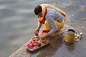 Pilgrim doing puja (Hindu devotional worship) in holy river Ganges, Varanasi, India
