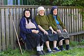 Three elderly ladies on a bench, Botiza, Maramures, Romania