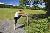 Jogger or runner stopping to stretch by a field and country road