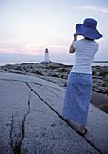 lady photographer at peggys cove lighthouse nova scotia canada