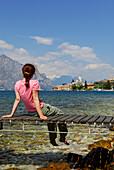Woman sitting on landing stage at lake Garda, Malcesine, Veneto, Italy