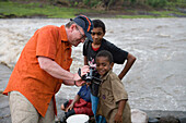 Tourist showing pictures on his video camera to fijian boys, Navala, Viti Levu, Fiji Islands, South Pacific, Oceania