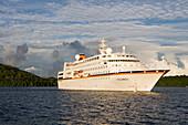 Cruiseship MV Columbus raising anchor in the light of the evening sun, Vava'u archipelago, Tonga, South Pacific, Oceania