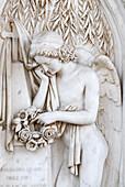 Angel of marble holding wreath of flowers in hands, San Abbondino graveyard, Gentilino, Lugano, Ticino, Switzerland