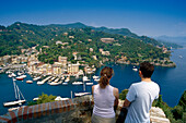 Young couple looking down at the marina, Portofino, Liguria, Italian Riviera, Italy, Europe