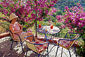 Laughing woman with cocktail and blooming plant on the terrace of a bar, Lindos, Island of Rhodes, Greece, Europe