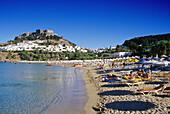 Blick auf Bucht mit Strand, Ort und Akropolis unter blauem Himmel, Lindos, Rhodos, Griechenland, Europa