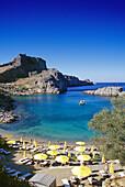 Sunshades on the beach of Agios Pavlos Bay under blue sky, Acropolis, Lindos, Island of Rhodes, Greece, Europe