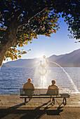 Mann und Frau auf einer Bank am Seeufer, Ascona, Lago Maggiore, Tessin, Schweiz, Europa