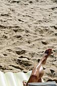 Mans legs on the beach