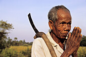Old man with a traditional knife, joigning hands for the traditionnal cambodian salutation, Cambodia